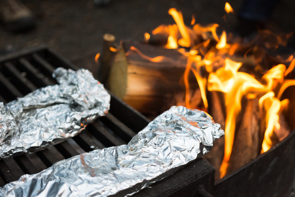 tin foil hobo packets on campfire grate over fire