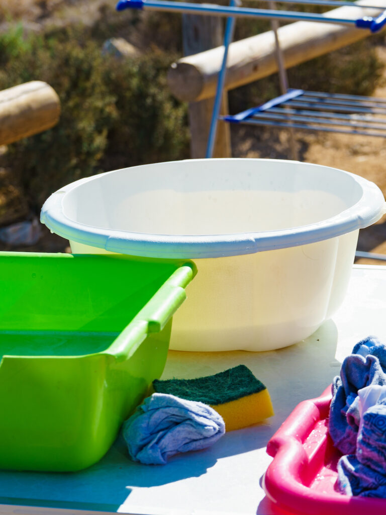 bowls of soapy water to wash clothes outside