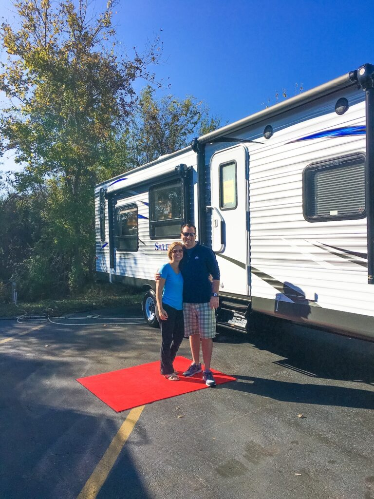 man and woman standing in front of new RV with red carpet