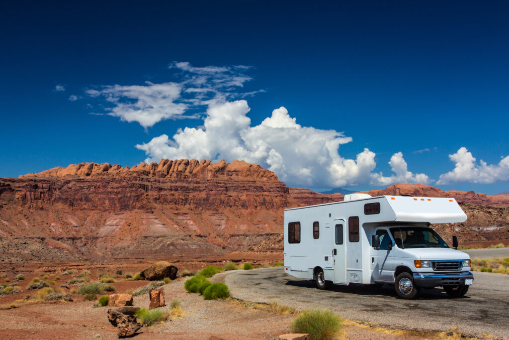 white rv parked in front of red rocks and blue sky