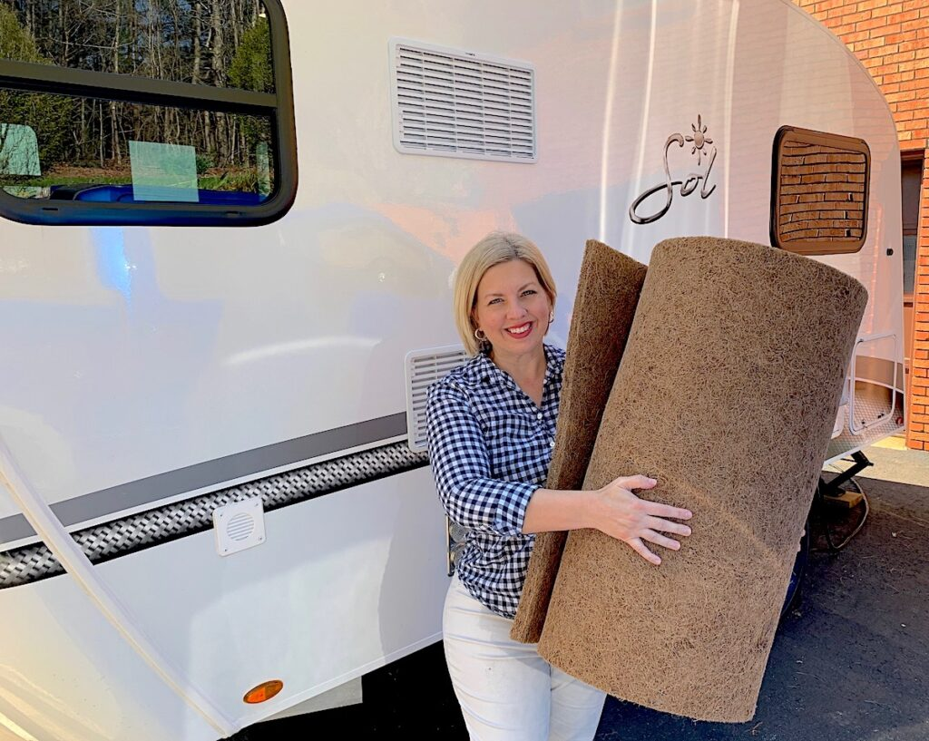 woman holding coir bed mat next to RV