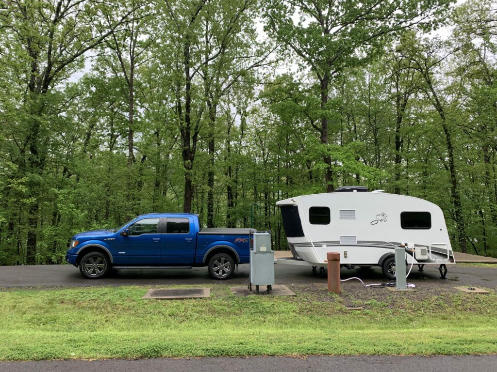 truck and small travel trailer parked in campsite
