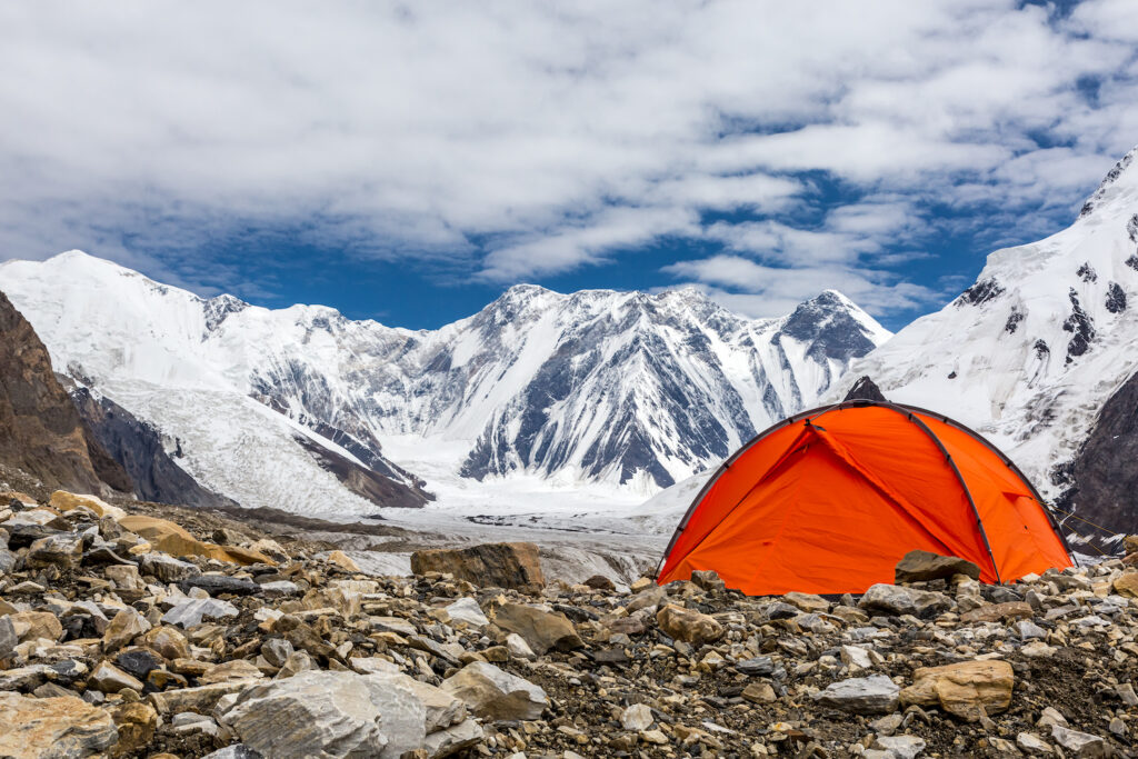 orange camping tent on rocky side of mountain with glaciers in distance